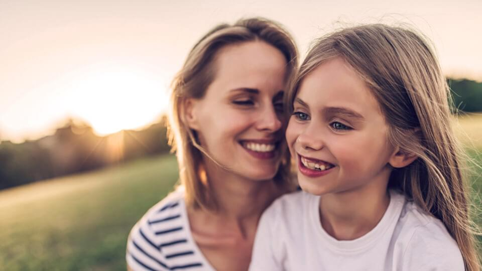 A mother and her daughter outside on a sunny evening smiling together