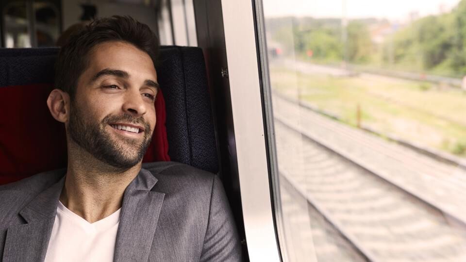 A man in a blazer on a train smiling and looking out of the window