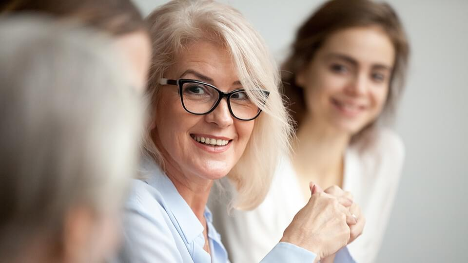 Smiling aged businesswoman in glasses looking at colleague at team meeting, happy attentive female team leader listening to new project idea, coach mentor teacher excited by interesting